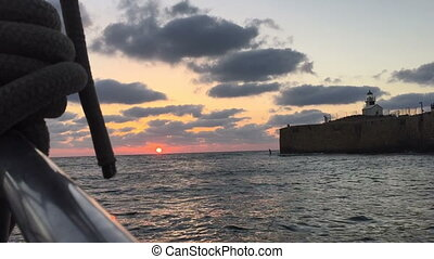 Sailing on sea during sunset with Acre view - Shot of...