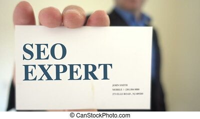 SEO Expert Holds a Business card - Shot of SEO Expert Holds...