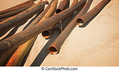 Rusty Steel Pipes Scattered in the Sand - Heap of rusty,...