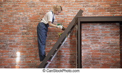 woman stands on stairs painting brown paint step indoors....