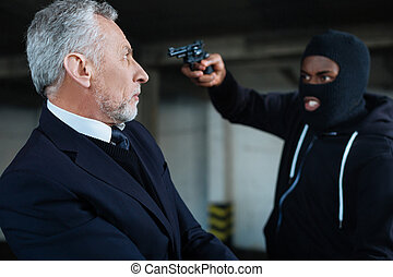Serious shocked man being at gunpoint - Dangerous situation....