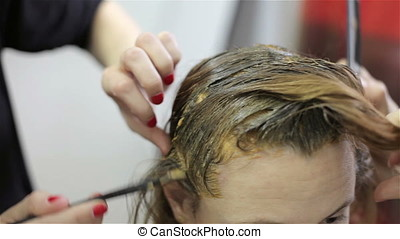 Woman is coloring her hair in salon