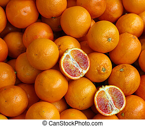 Ripe oranges and an orange cut in the stall of greengrocer -...