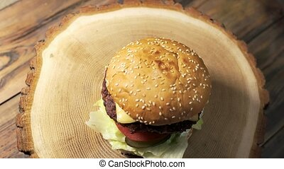 Burger on wooden board rotating. Top view of fresh...