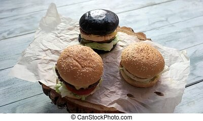 Burgers on wooden board rotating. Dark and light buns....