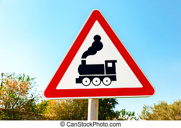 Traffic warning sign with train symbol against the blue sky...