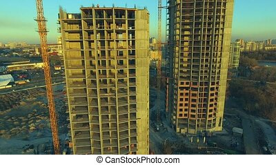 Aerial shot of construction site with cranes and workers at...