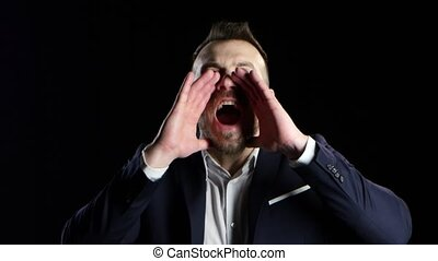 Businessman yells with his hands to his face, black background