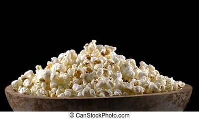 popcorn in a wooden bowl rotates on a black background,...