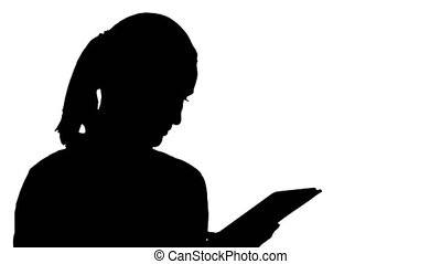 Silhouette Portrait of a young woman using a tablet. Close...