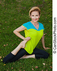 Healthy woman is doing stretching at the park. Healthy lifestyle