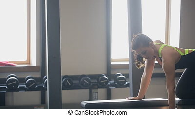 Young woman do exercise with dumbbell in fitness club....