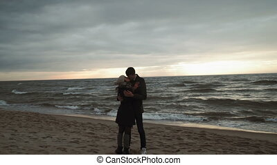 Young couple Posing for woman photographer, sunset photo session looking at the sea, walking the beach, coat and hat, Baltic or Iceland cold weather