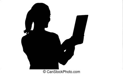 Silhouette Positive businesswoman is talking on the skype with partners on tablet.