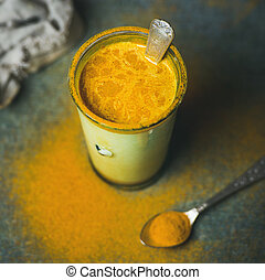 Golden milk with turmeric powder in glass, square crop -...