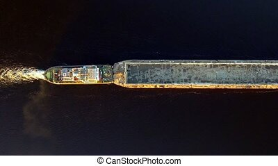 Aerial view of tug boat pushing empty barge.