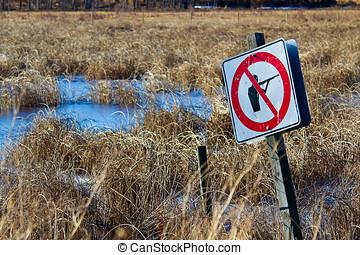 Shot up No Shooting sign along a nature path.