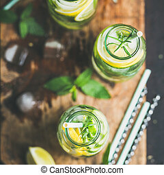 Healthy infused citrus sassi water in glass bottles, square...