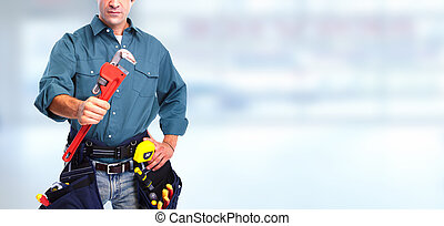 Plumber with wrench. - Hand of plumber with wrench over blue...