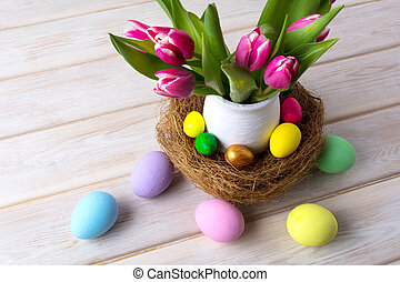 Easter table centerpiece with multicolored eggs in nest -...