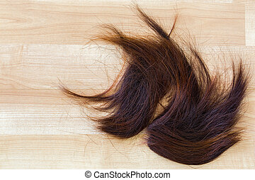 Bunch of trimmed cut off reddish brown hair on wooden floor...