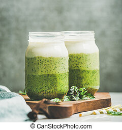 Ombre layered green smoothies with mint in jars, square crop...