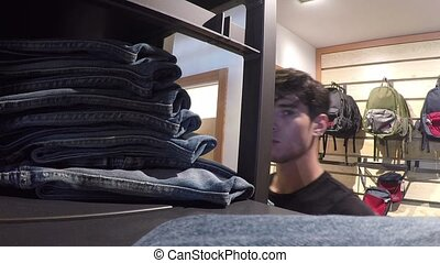 Young man choosing clothes in store - Side view of young...