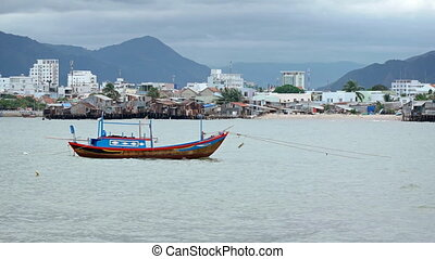 Wooden Fishing Boat Anchored near an Impoverished Community in Vietnam