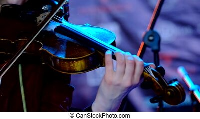 Young woman playing the violin close up