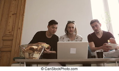 Friends hanging out together and watching a movie at laptop