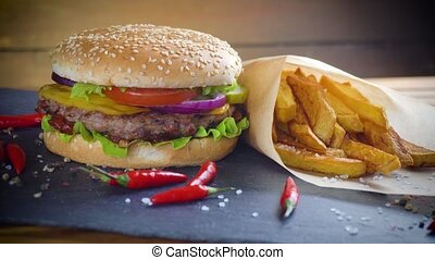 Tasty homemade hamburger with potatos served on stone plate...