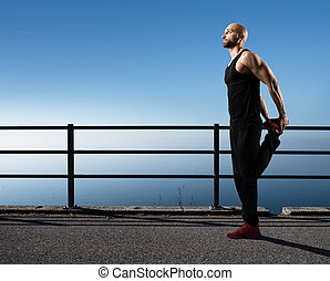 Stretching post workout - Muscular and athletic man in a...