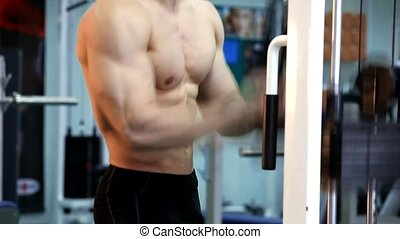 Young athletic man execute  muscle exercises