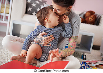 Mother kissing and hugging baby boy