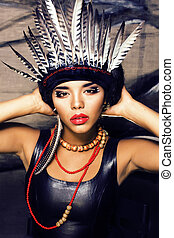 young pretty woman with make up like red indian, futher in...