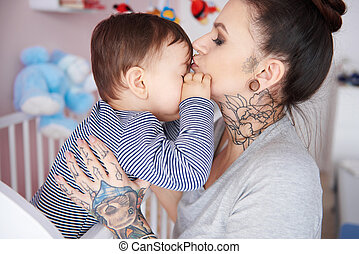 Mother kissing sleepy son on the forehead