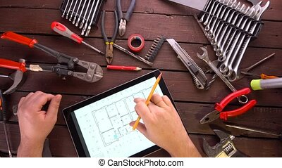 Mechanic engineer works with tablet on his desk between many...