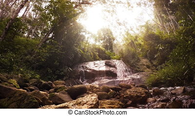Psychedelic natural landscape. Tropical rainforest, waterfall and sun rays