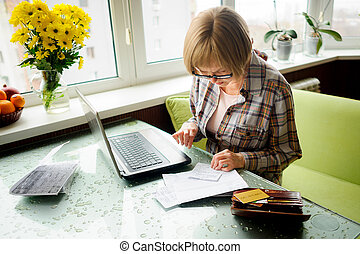 The elderly woman works behind the laptop. On a table...