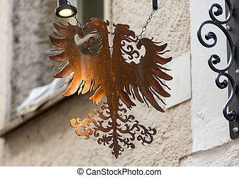 Wrought-iron guild sign hanging above a shop on...