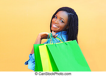 Fashion happy smiling african woman with shopping bags in city over colorful orange background
