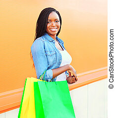 Fashion portrait smiling african woman with shopping bags in city over colorful orange background