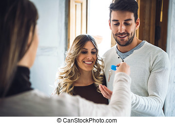 Happy couple getting keys from apartment