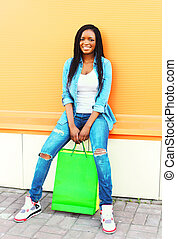 Fashion young smiling african woman with shopping bags in city over colorful orange background