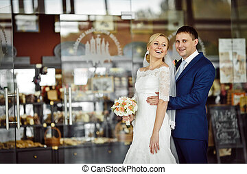 Laughing wedding couple stands in the front of a show-window