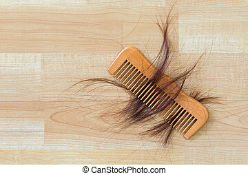 Hair on wooden comb on wooden floor with copyspace....