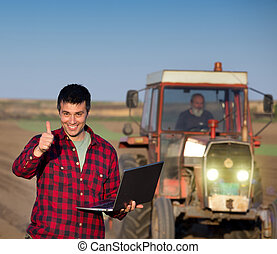 Satisfied farmer with laptop and tractor - Excited farmer...