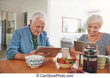 Smiling seniors using digital tablets over breakfast at home...