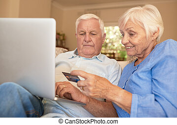Happy seniors shopping online with a credit card from home