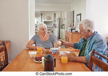 Smiling seniors enjoying a healthy breakfast at home...